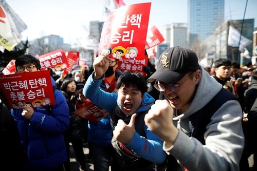Một số người vui mừng khi biết tin bà Park bị phế truất. Ảnh: Reuters