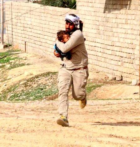 Chiến binh PMU ôm em bé trước khi trúng đạn bắn tỉa của IS. Ảnh: Almasdar news.