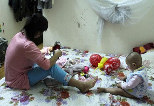 Mưa ẩm kéo dài khiến chị Thanh mỗi tối phải mất cả tiếng đồng hồ hong khô trang phục. Ảnh: Phan Dương.