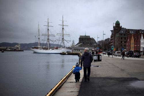 Một người đàn ông dắt em bé dọc bến cảng thị trấn Bergen, tây nam Na Uy. Ảnh: Reuters