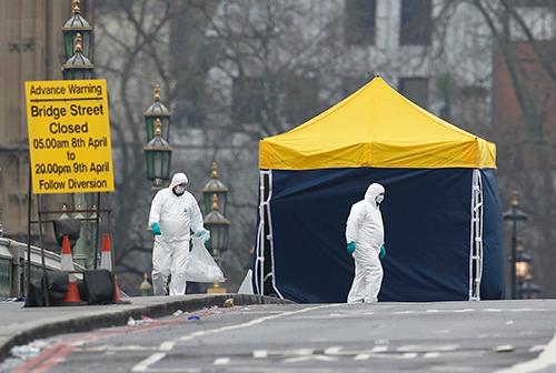Cảnh sát và các quan chức pháp y làm việc trên cầu Westminster, hiện trường vụ tấn công, vào sáng nay. Ảnh: Reuters