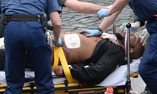 Khalid Masood được cấp cứu bên ngoài quốc hội trong khi cảnh sát có vũ trang đứng canh. Ảnh: PA