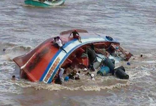 Chiếc tàu chở hàng chục người bị lật úp khi cách bờ vài trăm mét. Ảnh: Hiếu Hà.