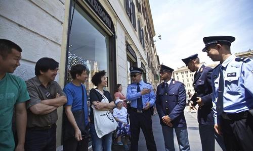 Cảnh sát Trung Quốc, Italy trò chuyện với du khách. Ảnh: Xinhua