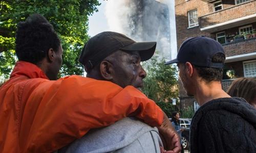 Mọi người an ủi người đàn ông da màu có thân nhân trong tòa tháp bị cháy. Ảnh: CNN