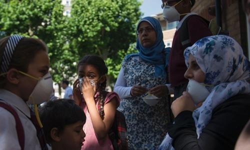Trẻ em đeo khẩu trang chống khói độc sau vụ cháy ở London. Ảnh: CNN