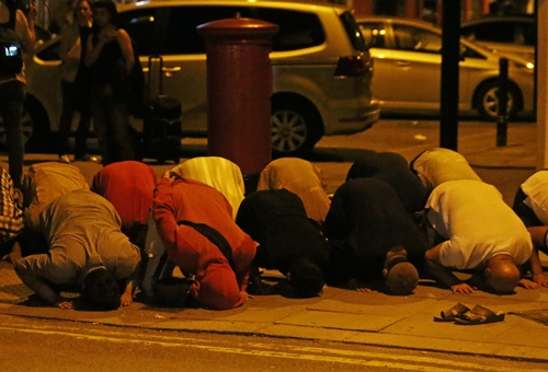 Nhiều người cầu nguyện gần thánh đường sau vụ đâm xe. Ảnh: Reuters