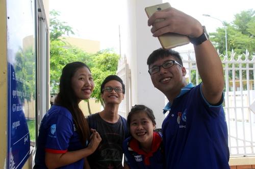 Thí sinh Đồng Nai thỏa mái chụp ảnh cùng các tình nguyện viên sau khi kết thúc kỳ thi. Ảnh: Phước Tuấn