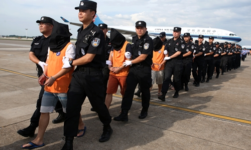 Chinese police officers escort a group of Chinese nationals suspected of telecom fraud after they were deported from Cambodia, at Changsha Huanghua International Airport in Changsha, Hunan province, China July 6, 2017.