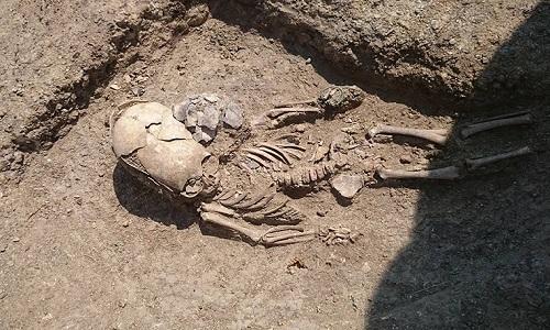 Hài cốt với hộp sọ dài đặc biệt của bé trai. Ảnh: archae.ru.