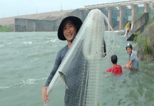 Người dân quăng lưới bắt cá dưới đập khi hồ Trị An xả lũ