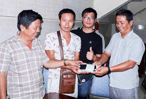 Tài xế Thiện (bên phải) cùng đại diện hãng xe buýt trao trả hơn 60 triệu đồng cho du khách Trung Quốc đánh rơi. Ảnh: Ạn