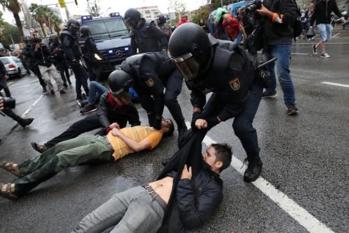 Lực lượng cảnh sát bán quân sự Tây Ban Nha kéo người biểu tình khỏi điểm bỏ phiếu trưng cầu dân ý ở Catalonia hôm 1/10. Ảnh: Reuters.