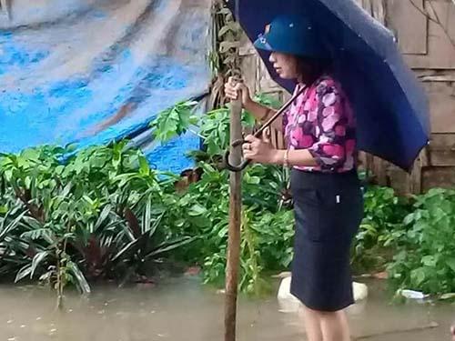 Bà Tâm đội mũ cối, cầm ô và mặc váy công sở đi kiểm tra ngập lụt. Ảnh: FB.
