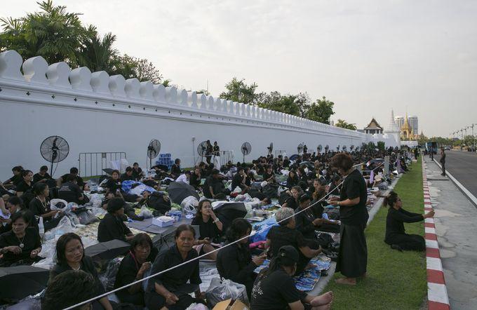 Người dân ngồi dọc tuyến đường bên ngoài Đại Cung điện ở Bangkok để chờ đón linh cữu nhà vua đi qua. Ảnh: AP.