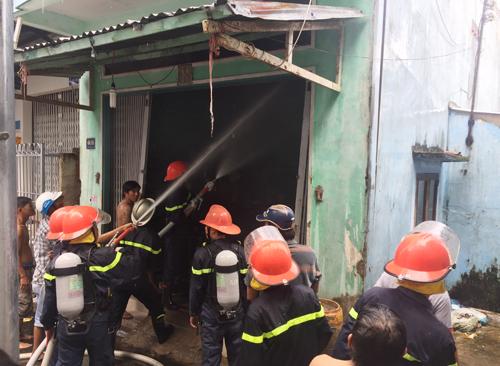 Cảnh sát cùng người dân phá cửa đưa cụ ông thoát ra ngoài rồi phung nước khống chế đám cháy. Ảnh: Phúc Hưng.