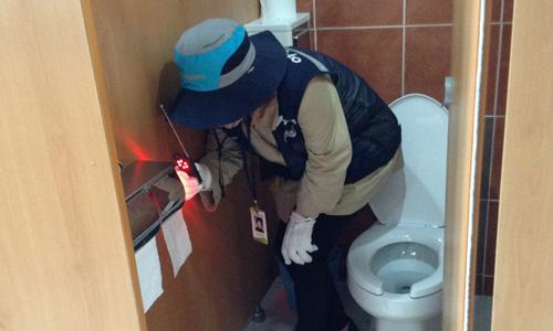 Lực lượng chuyên trách của Hàn Quốc dò camera nhìn trộm trong một phòng vệ sinh công cộng. Ảnh: Korea Times.