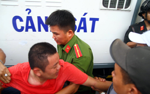 Một người bị cảnh sát áp giải lên xe. Ảnh: Hoàng Nam.
