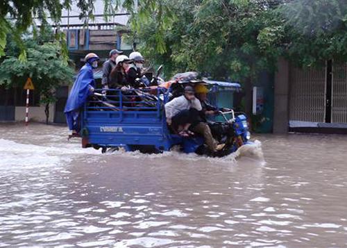 Nhiều tuyến đường ở Quy Nhơn bị ngập sâu, người dân phải tăng bo xe ba gác.