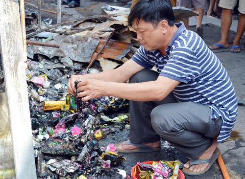 Tiểu thương tìm một ít tài sản còn sót lại sau vụ cháy. Ảnh: Phúc Hưng.