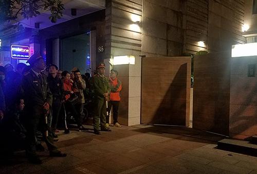 19h, cánh cổng lối vào gara biệt thự hé mở, nhiều người tập trung theo dõi. Ảnh: Nguyễn Đông.