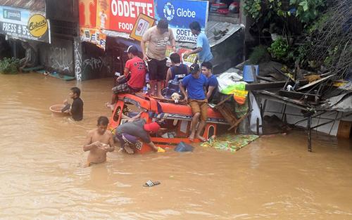Người dân ngồi trên một chiếc xe ngập tới nóc trên một con phố ở Cagayan de Oro, thành phố phía bắc đảo Mindanao hôm 22/12.Ảnh: Reuters.