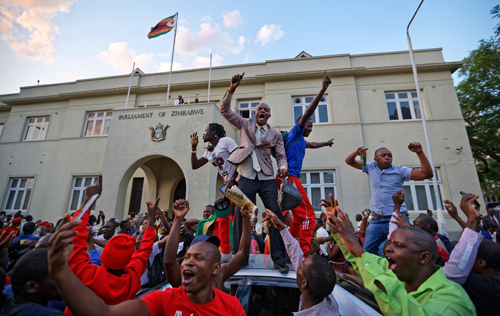 Người dân Zimbabweans ăn mừng ông Mugabe từ chức bên ngoài quốc hội ở thủ đô Harare. Ảnh: AP.