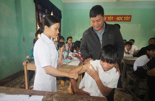 Thầy Nguyễn Khắc Điệpđộng viên học sinh tiêm văcxinbệnh bạch hầu. Ảnh:Đắc Thành.
