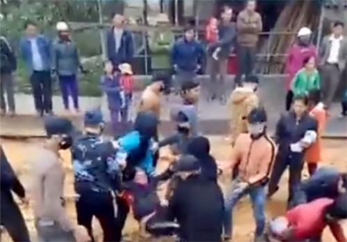 Một người phụ nữ bị nhóm thanh niên bồng ra khỏi công trường. Ảnh:Cắt từ video