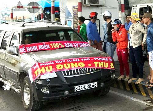 Tài xế đậu xe, căng băng rôn yêu cầu chủ đầu tư trạm BOT Cần Thơ - Phụng Hiệp thu đúng - thu đủ. Ảnh: Cửu Long.