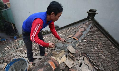 Dân làng dọn đất rác phủ kín nhà sau vụ nổ kho đạn