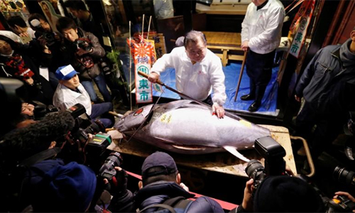 Kiyomura Cos President Kiyoshi Kimura (C), who runs a chain of sushi restaurants Sushi Zanmai, poses with a 190 kg bluefin tuna, priced with a 30.4 million yen bid at the fish markets first tuna auction this year at his sushi restaurant outside Tsukiji fish market in Tokyo, Japan, January 5, 2018. REUTERS/Toru Hanai