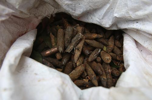 Đầu đạn thu gom được cho vào bao tải, đưa lên ôtô chở đến nơi xử lý. Ảnh: Ngọc Thành.