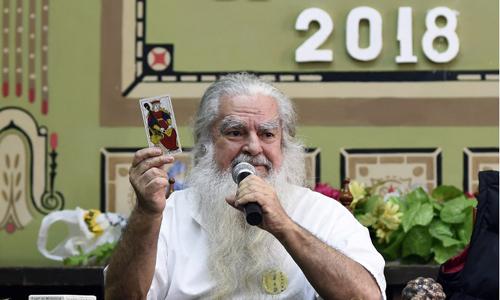 Thầy phù thủy Antonio Vazquez giải thích thông điệp của một lá bài Tarot. Ảnh: AFP.