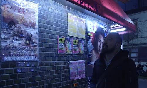Một người đàn ông đi qua bức tường dán đầy quảng cáo mại dâm nam ở Nicho, Tokyo. Ảnh: SCMP.