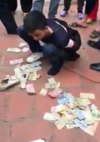 Hoàng Văn Mạnh bị người dânbắt quả tang cùng số tiền công đức trộmtại đền Long Bì, xã Đoàn Lập, huyện Tiên Lãng. Ảnh:cắt từ video clip