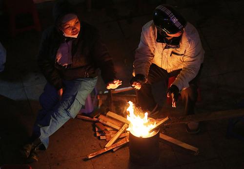 Về đêmHà Nội chỉ 10 độ C, những người làm việc ngoài đường phải đốt lửa sưởi ấm. Ảnh: Ngọc Thành.