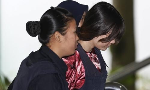 Cảnh sát áp giải Đoàn Thị Hương tới tòa án ngày 22/1. Ảnh: AP.