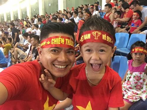 Anh Nguyễn Thành Chung và con trai cổ vũ Việt Nam trong một lần đội tuyển thi đấu trên sân Mỹ Đình năm 2017. Ảnh: NVCC