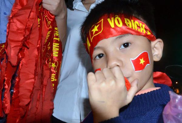 Bé trai mang theo kèn để mừng chiến thắng đội tuyển U23. Ảnh: Phạm Linh.