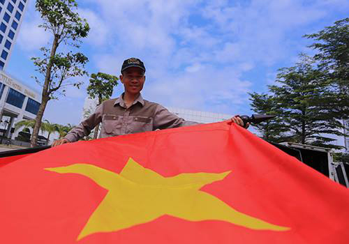 Một nhân viên khách sạn chuẩn bị cờ trước trận đấu. Ảnh: Nguyễn Đông.