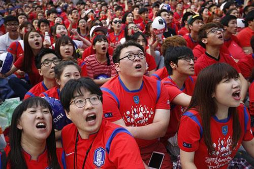 Người dân Seoul theo dõi một trận cầu qua màn hình rộng. Ảnh:Reuters.