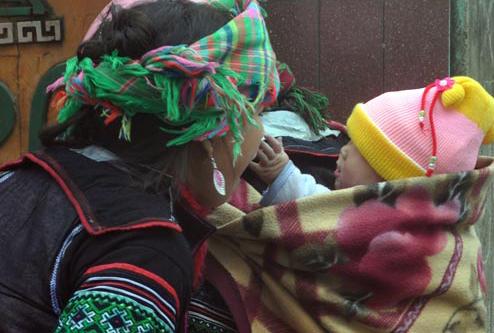 Trẻ vùng cao được mẹ địu trong chăn ấm. Ảnh: Anh Lâm