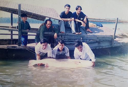 Những người con của ông Lới bên con cá sủ vàng nặng 67 kg, bắt được năm 1998. Ảnh:Đức Hùng chụp lại.