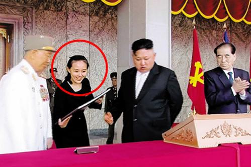 Kim Yo-jong đưa cho ông Kim Jong-un xem tài liệu trong lễ duyệt binh năm 2017. Ảnh: KCTV.
