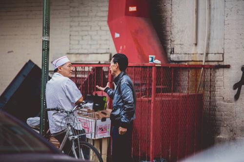 Hai người đàn ông đứng nói chuyện sau một nhà hàng Trung Hoa trên phốBensonhurst, Brooklyn, New York. Anrh: Kenn Tam.