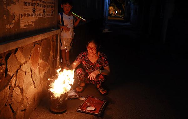 Ảnh 2: Tại con hẻm trên đường Hoàng Hoa Thám (quận Tân Bình), bà Y đốt vàng mã rước ông bà về trước khi làm lễ cũng giao thừa.