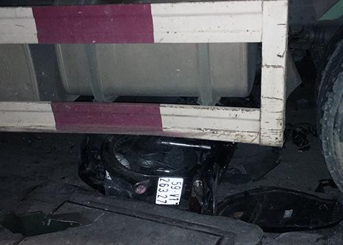 Một xe máy nằm dưới gầm ôtô ben. Ảnh: Sơn Hoà