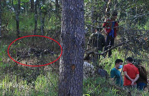 Cảnh sát khám nghiệm hiện trường nơi thi thể nạn nhân (khoanh tròn đỏ) cháy đen. Ảnh: Khánh Hương.