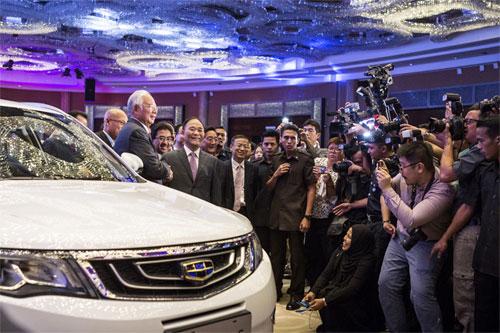 Lý Thư Phúc bắt tay thủ tướng Malaysia sau khi Geely mua cổ phần của hãng Proton. Ảnh: Bloomberg.